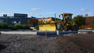 En gul traktor står på en sandplan. I bakgrunden syns Nickby Hjärta.