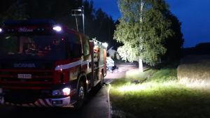 En brandbil står på en mörk väg.