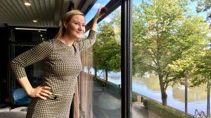 Minja Westerlund tittar ut ur ett fönster.