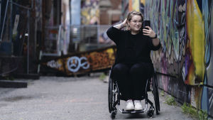 Bloggaaja Anna Giss ottaa itsestään selfietä vanhalla tehdasalueella. Hänen ympärillään olevien tiilirakennusten seinät ovat täynnä katutaidetta.