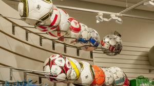 Fotbollar uppställda bredvid varandra i en sportaffär.