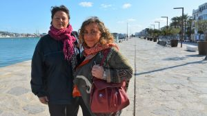 Två kvinnor står på en strandpromenad.