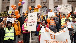 Postanställda i orange jackor och neongul västar står på riksdagshusets trappor med skyltar och ballonger och demonstrerar.