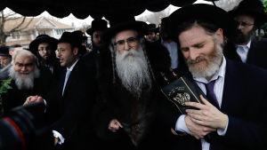 Juutalaiset kokoontuivat seremoniaan rabbi Chaim Rottenbergin kodin edustalle 29. joulukuuta. Päivää aiemmin taloon tunkeutunut mies puukotti viittä ihmistä.
