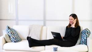 Paula Koskinen Sandberg istuu sohvalla ja puhuu puhelimeen.
