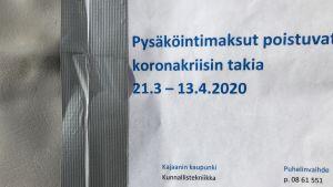 Pysäköintiautomaatin kylkeen liimattu ilmoitus jossa kerrotaan pysäköintimaksujen päättämisestä