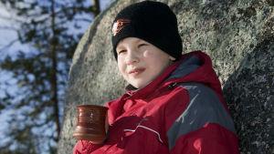 pikkupoika nojaa kiveen höyryävä muki kädessä