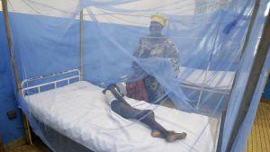 Kvinna vakar över ett barn som insjuknat i malaria