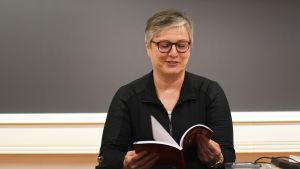 Anna-Lena Juslin bläddrar i Maols tabeller.