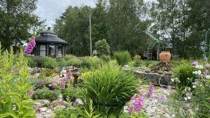 En trädgård med ett mörkt lusthus till vänster och en stenfontän till höger.
