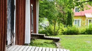 Till vänster i färgrunden en röd boda med två dörrar och trappor. Till höger, bakom lite buskar och träd, syns en gul trävilla.
