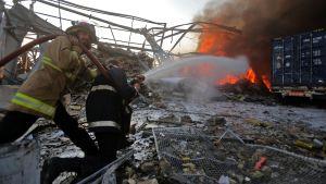 Räddningspersonal försöker släcka bränderna som orsakats av en explosion i Beirut i Libanon.