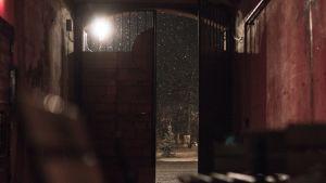 Öppen dörr i motljus med snöfall utanför