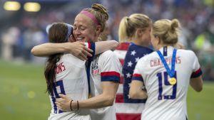 Becky Sauerbrunn ler mot kramar om en lagkamrat och ler lyckligt.