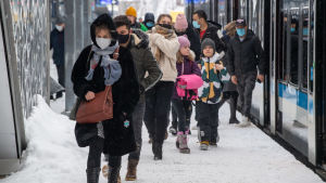 Vinterklädda passagerare på tågperrong i snöväder.