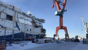 Halvfärdigt fartyg vid kaj intill en orange lyftkran. Det finns snö på marken och himlen är blå.