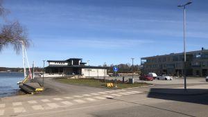 En parkeringsplats framför en restaurang och ett bostadshus i Norra hamnen i Ekenäs.