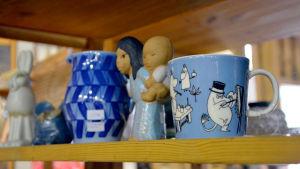 En blå muminmugg står på en hylla. I bakgrunden syns föremål gjorda av Lisa Larsson.