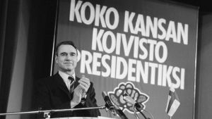 Mauno Koivisto står bakom ett podium och klappar.