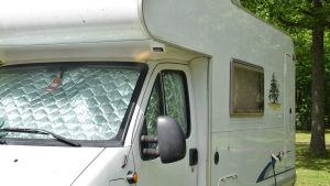 Husbil med gardinerna nerdragna och vindrutan täckt.