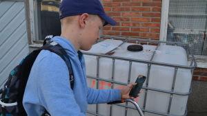 Eleven Walter Holmström med mobiltelefon i handen.