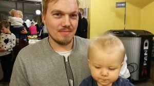 En pappa med sin pojke i famnen.