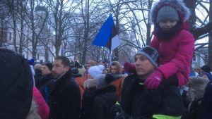 Människor som samlats för att se flagghissningen och sjunga Estlands nationalsång.