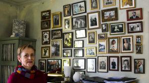 Kuvittaja Virpi Talvitie huoneessa, missä seinä on täynnä kuvatauluja.