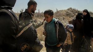 Civila får lämna Östra ghouta. En pojke med mobiltelefon i handen tillsammans med syriska regeringssoldater.