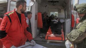 En kvinna ligger i en ambulans och får hjälpa av Röda halvmånen och internationella Röda korset.
