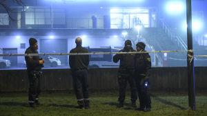 Fyra svenska poliser vid en avspärrad byggnad i mörkret.
