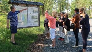 Calle Storm föreläser om Jungfrusunds flygfottilj framför en grupp människor i sommarväder.