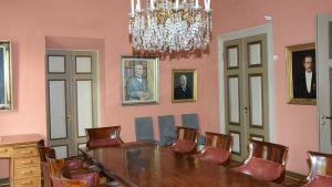 Ett långt bord i ett rum med tavlor på väggen.