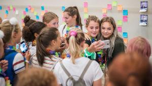 Amanda Edmundsson hälsar på sina fans. Flera unga kvinnor flockar runt Edmundsson. Edmundsson tar som bäst en selfie med ett fan.