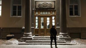 Entre till stor stenbyggnad. Trappor och utsmyckad dörr. Vid trappan snö och person som vandrar förbi.