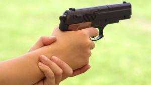 Lapsi tähtää käsiaseella, vain kädet ja ase kuvassa.