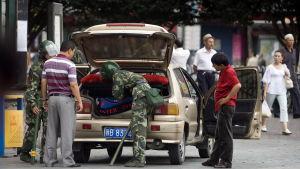 Kinesiska soldater undersöker en uigurisk mans bil
