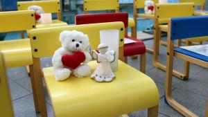 Gula stolar med små nallar, ljus och änglar, vilka symboliserar de barn och unga som under året fått cancer och de som dött i cancer.