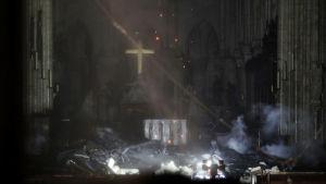 Insidan av Notre-Dame under branden. Golvet är täckt av bråte.