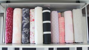 Outi Pyrhönen viikkaa pyykit kaapissa oleviin laatikoihin pystyyn.