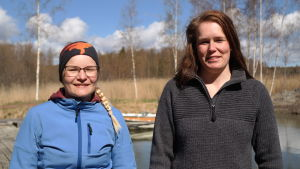 Sandra Bergqvist och Linda Sandström står på en strand med vatten, björkar och vass i bakgrunden