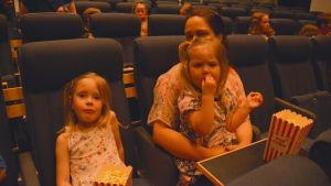 En mamma och två flickor sitter i en biosalong