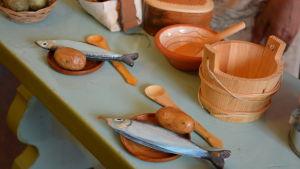På en bänk ligger två tallrikar med konstgjord fisk och potatis, i bakgrunden står det kärl gjorda av trä.