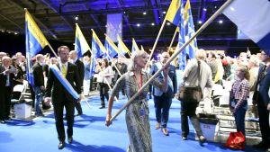 Partikongressen inleds med flaggmarsch, Laura Huhtasaari bär Finlands flagga.