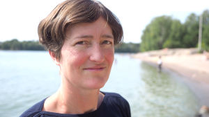 Havsforskaren Vivi Fleming-Lindberg står på en strand i Helsingfors och ser mot kameran.