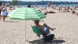 En man sitter på stranden under ett grönt parasoll.