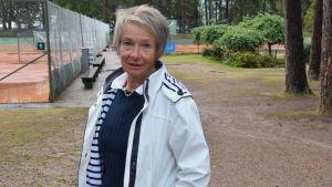 En kvinna i vit jacka står nära en tennisbana.