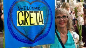 """Katherine med ett plakat med texten """"Welcome Greta""""."""