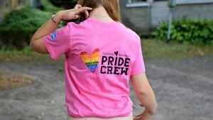 """Flicka står med ryggen mot kameran iklädd en rosa skjorta med texten """"Pride Crew""""."""