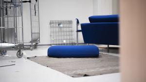 En kontorsbyggnad där saker ligger huller om buller. Byggnaden verkar inte vara i bruk, men lampan är ändå tänd. I rummet syns en soffa, en stol och en matta.